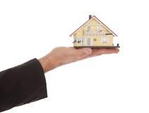 Modelo da terra arrendada do homem de negócios de uma casa nas mãos fotografia de stock royalty free