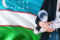 Modelo da terra arrendada da mulher do arquiteto do Uzbeque contra o fundo de ondulação da bandeira de Usbequistão Conceito da co imagem de stock royalty free