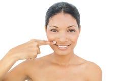 Modelo de cabelo preto de sorriso que aponta acima de seus bordos Imagem de Stock