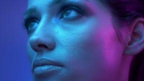 Modelo de forma fantástico com sombras do brilho em relógios coloridos das luzes de néon na perplexidade nos arredores filme