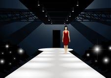 Modelo de forma no vestido vermelho que anda abaixo de uma passarela Imagens de Stock