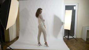 Modelo de forma novo atrativo com o cabelo longo que levanta em um estúdio profissional com fundo branco para um fotógrafo do est video estoque