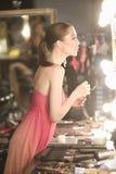 Modelo de forma In Pink Slip que olha o espelho do vestuario Fotos de Stock