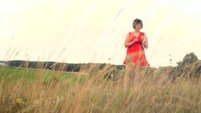 Modelo de forma positivo do tamanho no vídeo de movimento lento que anda na grama a mulher gorda na natureza na grama do campo fl video estoque