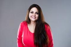Modelo de forma positivo feliz do tamanho no vestido vermelho, mulher gorda 'sexy' no fundo cinzento, conceito positivo do corpo fotos de stock royalty free