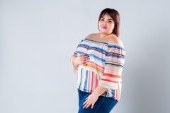 Modelo de forma positivo na roupa ocasional, mulher gorda do tamanho no fundo cinzento fotografia de stock royalty free