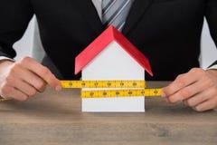 Modelo de Hand Measuring House del hombre de negocios fotos de archivo libres de regalías