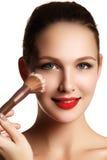 Modelo de la belleza con el cepillo del maquillaje Brillante compense el woma moreno fotografía de archivo libre de regalías