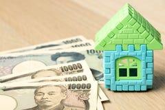 Modelo de la casa con el billete de banco de los yenes japoneses en el fondo de madera imagen de archivo libre de regalías