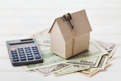 Modelo de la casa de la cartulina con llave, dólares de la calculadora y del efectivo Construcción de viviendas, préstamo, propie Imágenes de archivo libres de regalías