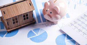 Modelo de la casa, hucha, calculadora con los gráficos financieros imagen de archivo