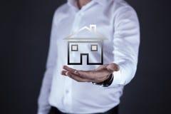 Modelo de la casa de la mano del hombre en pantalla foto de archivo