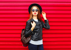 Modelo de la mujer bastante joven en el estilo de la roca del negro de la moda que presenta sobre rojo colorido vacío Foto de archivo libre de regalías