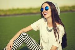 Modelo de la mujer en la ropa casual del inconformista del verano que presenta en fondo de la calle en el parque Imagen de archivo libre de regalías