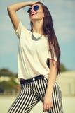 Modelo de la mujer en la ropa casual del inconformista del verano que presenta en fondo de la calle en el parque Foto de archivo