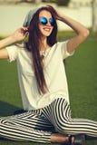 Modelo de la mujer en la ropa casual del inconformista del verano que presenta en fondo de la calle en el parque Foto de archivo libre de regalías