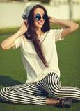 Modelo de la mujer en la ropa casual del inconformista del verano que presenta en fondo de la calle en el parque Imagen de archivo