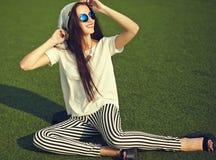 Modelo de la mujer en la ropa casual del inconformista del verano que presenta en fondo de la calle en el parque Fotografía de archivo