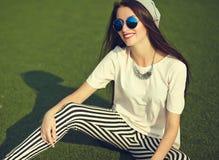 Modelo de la mujer en la ropa casual del inconformista del verano que presenta en fondo de la calle en el parque Imágenes de archivo libres de regalías