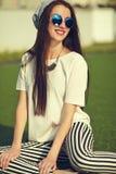 Modelo de la mujer en la ropa casual del inconformista del verano que presenta en fondo de la calle en el parque Fotos de archivo libres de regalías