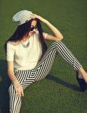 Modelo de la mujer en la ropa casual del inconformista del verano que presenta en fondo de la calle en el parque Imagenes de archivo