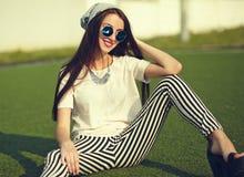 Modelo de la mujer en la ropa casual del inconformista del verano que presenta en fondo de la calle en el parque Fotos de archivo