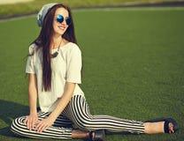 Modelo de la mujer en la ropa casual del inconformista del verano que presenta en fondo de la calle en el parque Fotografía de archivo libre de regalías