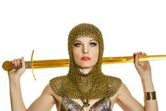 Modelo de la mujer joven en la armadura de vikingo con la espada Imagenes de archivo