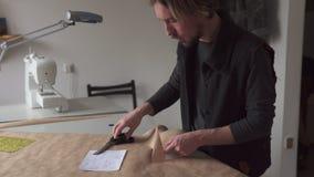 Modelo de la ropa del corte del diseñador del hombre según bosquejo creativo en el lugar de trabajo almacen de video