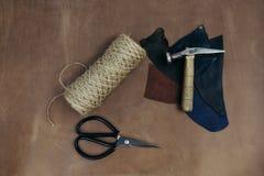 Modelo de las herramientas Martillo, tijeras en cuero Fondo con las herramientas y los accesorios de costura y que hacen punto Imagen de archivo