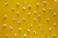 Modelo de las palomitas en fondo amarillo Visión superior Ponga en contraste el concepto palomitas en fondo del color fotografía de archivo