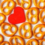 Modelo de los pretzeles del fondo del día de tarjeta del día de San Valentín y corazón rojo Fotografía de archivo