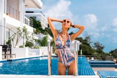 Modelo de lujo de la muchacha en la piscina de un hotel costoso en un traje de ba?o moderno a estrenar Apartamentos, chalet priva foto de archivo libre de regalías