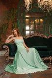 Modelo de lujo de la mujer en un vestido menta-coloreado que se sienta en un sofá del vintage Muchacha de la belleza con un maqui imagen de archivo