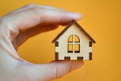 Modelo de madeira da casa do brinquedo na mão da mulher na opinião dianteira do fundo amarelo fotografia de stock