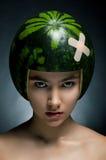 Modelo de manera hermoso con la sandía como sombrero duro Foto de archivo