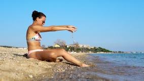 Modelo de moda adolescente que se relaja en orilla de la playa del verano Foto de archivo