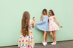 Modelo de moda adulto joven que toma la foto con un teléfono elegante Imagenes de archivo