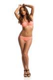 Modelo de moda atractivo In Pink Swimsuit que presenta con los brazos aumentados fotografía de archivo