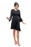 Modelo de moda bastante lindo en el vestido negro que camina y que mira de equilibrio abajo Imagen de archivo