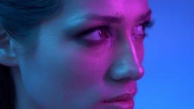 Modelo de moda cósmico en las luces de neón coloridas que miran fijo rightwards en estudio almacen de metraje de vídeo