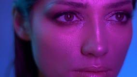 Modelo de moda cósmico en las luces de neón púrpuras que se mueven lentamente y que miran seriamente en alguna parte en estudi almacen de metraje de vídeo