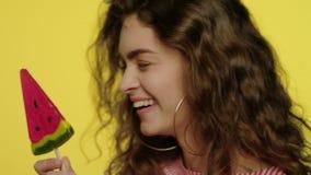 Modelo de moda con el caramelo que mira in camera Mujer de risa que come la piruleta de la diversi?n almacen de metraje de vídeo