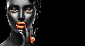 Modelo de moda con la piel negra, los labios de oro, las pestañas y la joyería - anillo de oro a mano En fondo negro foto de archivo libre de regalías