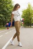Modelo de moda de la chica joven que presenta con longboard en el parque en la pista Forma de vida al aire libre Foto de archivo libre de regalías