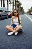 Modelo de moda de moda que presenta con el tablero del patín que lleva las gafas de sol coloridas Fotos de archivo libres de regalías