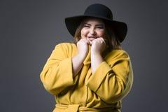 Modelo de moda del tamaño extra grande en la capa amarilla y el sombrero negro, mujer gorda en fondo gris, cuerpo femenino gordo foto de archivo
