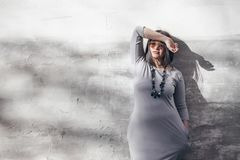 Modelo de moda del tamaño extra grande sobre la pared gris de la calle Foto de archivo