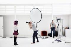 Modelo de moda del tiroteo del fotógrafo en sesión fotográfica Foto de archivo libre de regalías