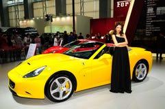 Modelo de moda en el coche de deportes convertible de Ferrari California 30 Foto de archivo